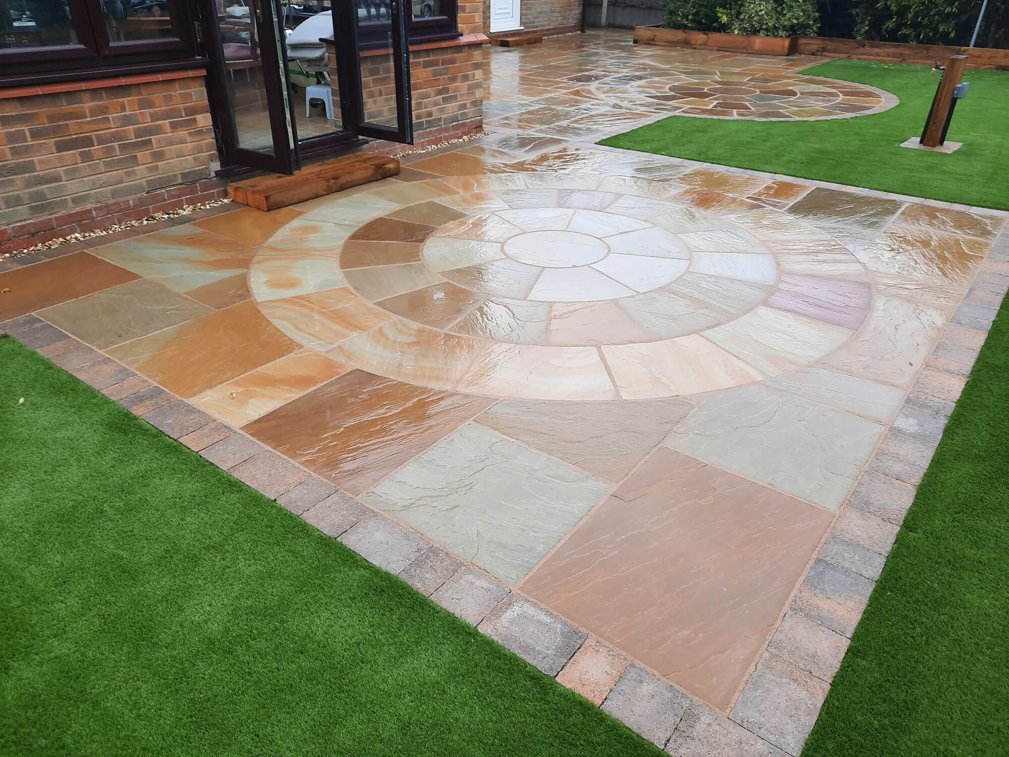 Artificial Grass installation with a Sandstone patio