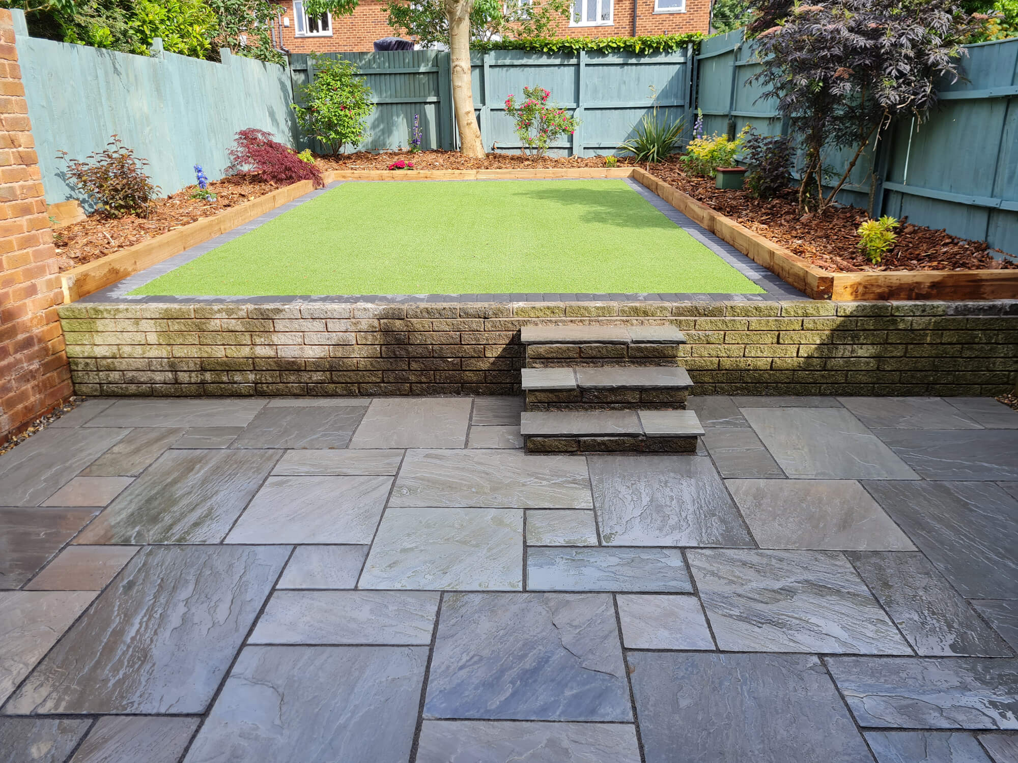 JD Landscapes Garden and Patio Natural Stone Patio in Grey with Artificial Grass and Sleeper Borders