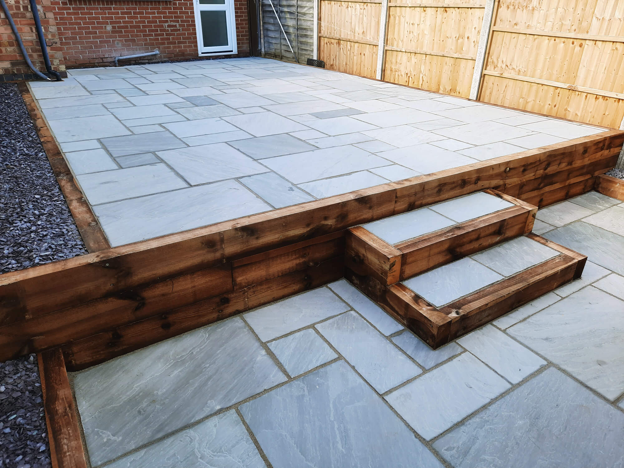 JD Landscapes Garden with Timber Sleeper Retaining Wall with Steps Natural Stone Slabs in Grey